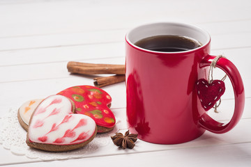Cup of black tea with cookies in the shape of heart