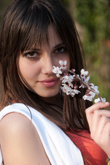 Teenage romantic girl holding branch of almond in blossom