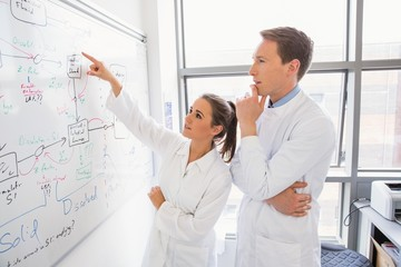 Science student and lecturer looking at whiteboard