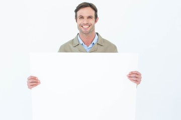 Happy delivery man holding blank billboard