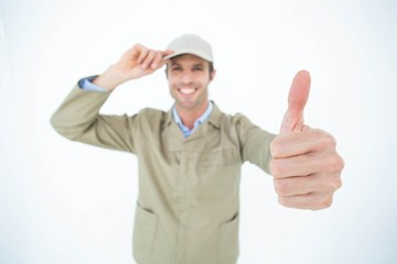 Delivery man wearing cap while gesturing thumbs up