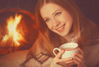 happy girl relax by fireplace with mug of tea, coffee