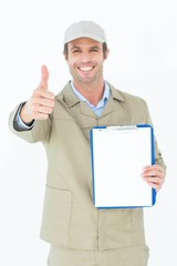 Delivery man gesturing thumbs up while showing clipboard