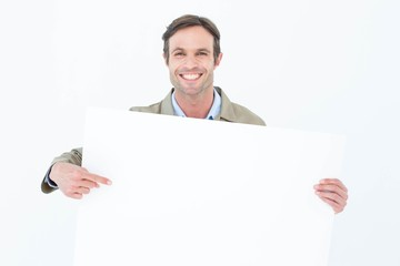 Happy delivery man pointing at blank billboard