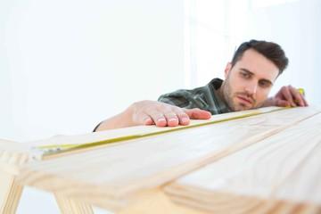 Worker measuring wooden plank