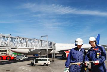 airplane mechanics with airplane and passenger bridge