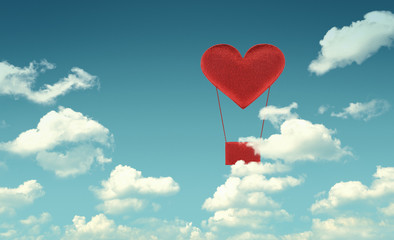 Fabric red heart air balloon on blue sky background