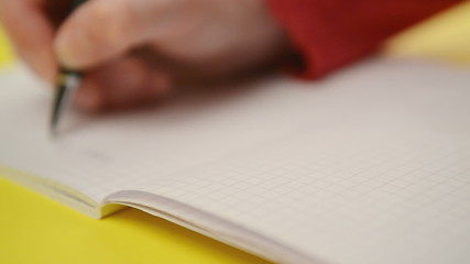 Woman writing notes in notebook, out of focus