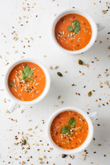 fresh tomatoe soup in cups with seeds and parsley