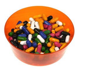 Many colorful sugar candies in an orange bowl