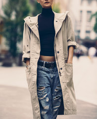 Girl on the street. urban style. Cloak and ripped jeans.
