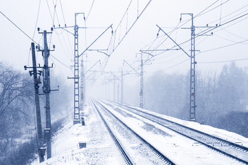 Empty electric railroad in winter forest