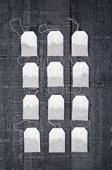 Teabags on black wooden background