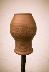 Clay pot with a pattern on a wooden stick on a light background.
