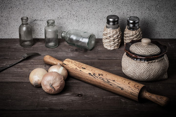 Onion, salt, pepper, rolling pin, old bottles and fork on the ol