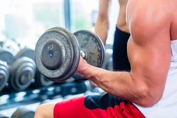 Mann trainiert Bizeps mit Hantel im Fitnessstudio