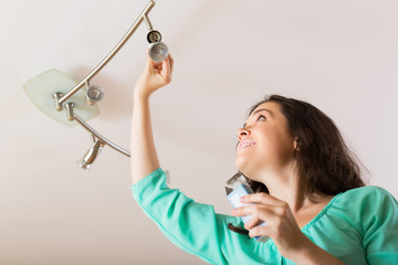 Girl changing light bulb