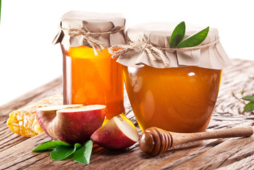 Glass cans full of honey and apples.