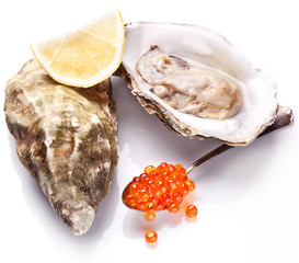 Raw oyster,lemon and red caviar on a whte background.