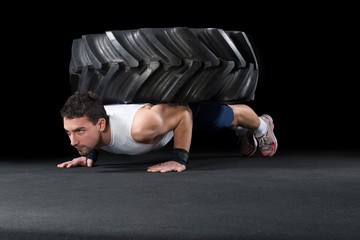 Muscular Men use big tire as part of Crossfit Training