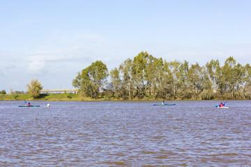 Gente joven practicando piragüismo en el rio