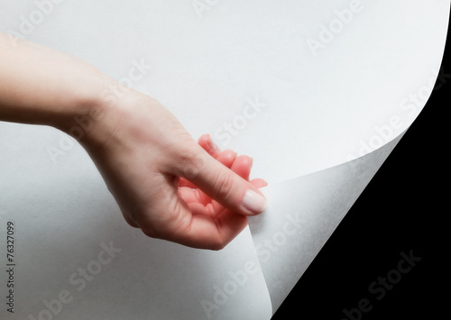 Hand pulling a paper corner to uncover, reveal something - 76327099