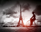 Man on retro bicycle next to Effel Tower, Paris, France.
