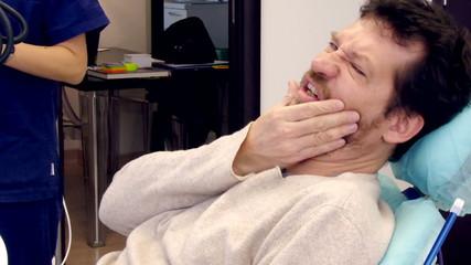 Man feeling strong teeth ache at dentist studio
