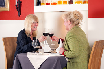Two blond woman toasting with red wine.