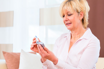 Seniorin mit Diabetes benutzt Blutzuckermessgerät