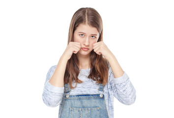 Sad young fashion girl in jeans overalls isolated