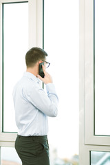 Handsome young businessman using mobile phone over blurred backg