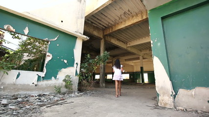 Little girl walking in in abandoned factory. Tracking shot.