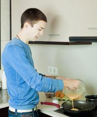 Guy pouring dough  in frying pan