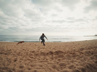 Man runs with his dog on beach
