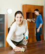 woman with husband cleaning wooden furiture