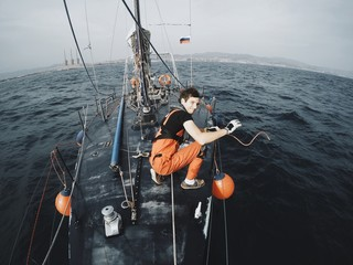 Sailor unties the rope on board