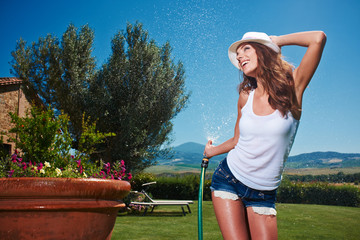 Young sexy woman is watering a garden.