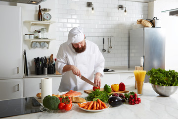 Professional male cook cut vegetables in big modern the kitchen