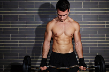 Muscular and sexy man exercising his abs with barbell at gym