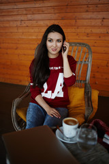 Attractive young woman talking on her cell phone sitting in cafe