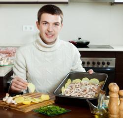 Guy cooking meat in roasting pan