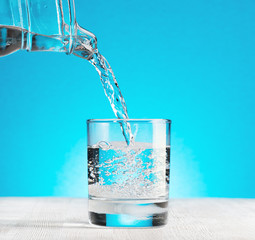 Water pouring into a glass on blue background
