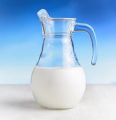 Jug of milk on sky background. Half full pitcher