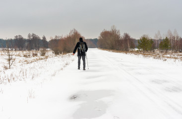 Winter landscape with country road and lonely wanderer
