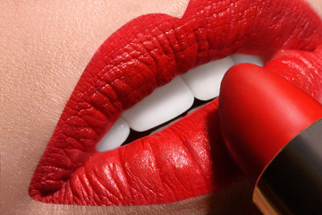 Sensual open mouth  with red tube of lipstick