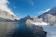 cold fresh alpine lake in austrian mountains with snow