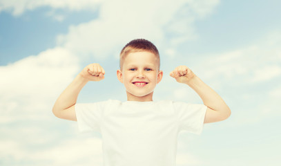 happy little boy in white t-shirt flexing biceps