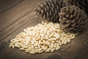 clean pine nuts on wooden table with pine cones