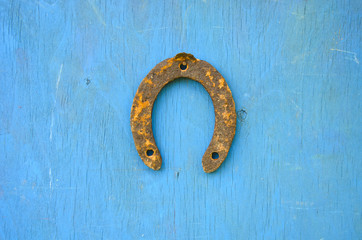 one rusty ancient horseshoe on wooden wall